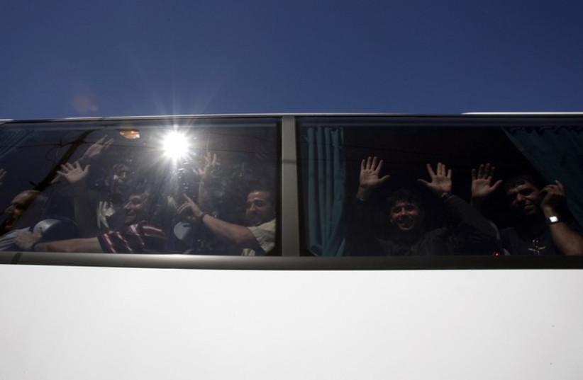 Palestinian prisoners who were released from Israeli prisons as part of a prisoners exchange deal between Israel and Hamas wave from a bus  (photo credit: REUTERS)