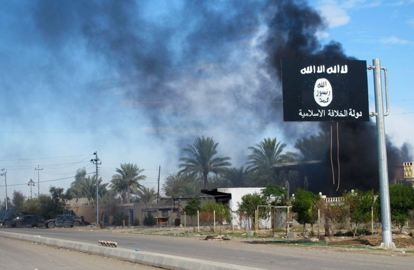 Smoke raises behind an Islamic State flag in Iraq  (photo credit: REUTERS)