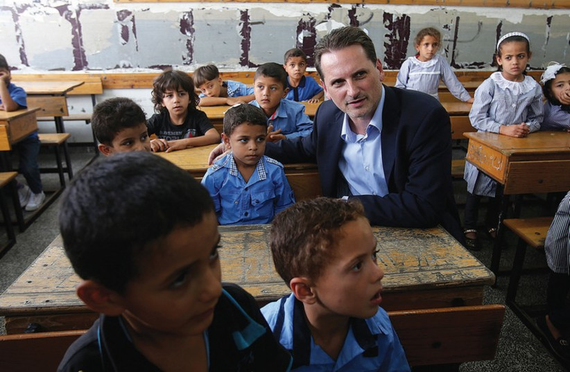 UNRWA Commissioner-General Pierre Krahenbuhl sits with students at a UN-run school in Khan Yunis in the Gaza Strip  in the Gaza Strip earlier this year (photo credit: REUTERS)