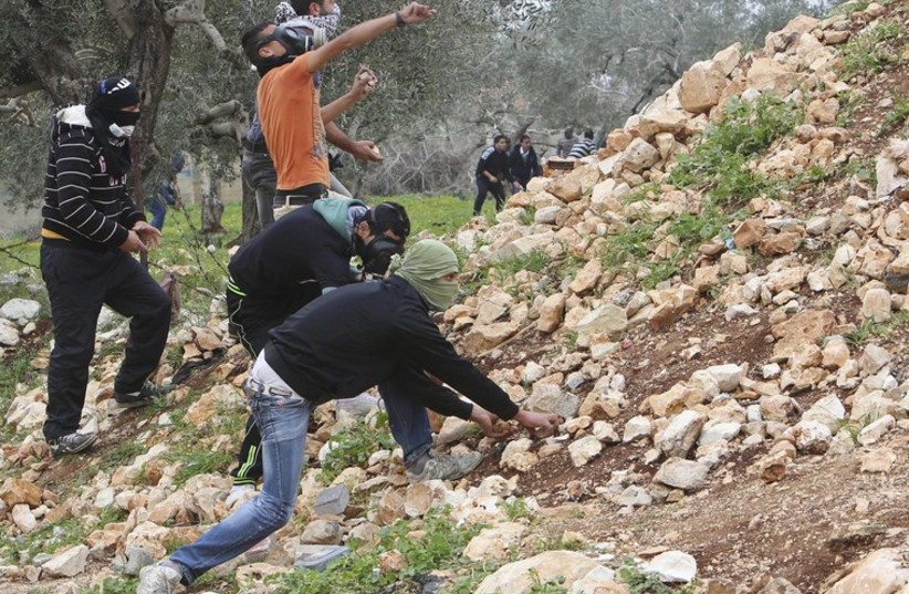 Palestinian protesters pick up stones to throw at Israeli troops during clashes near Nablus (photo credit: REUTERS)