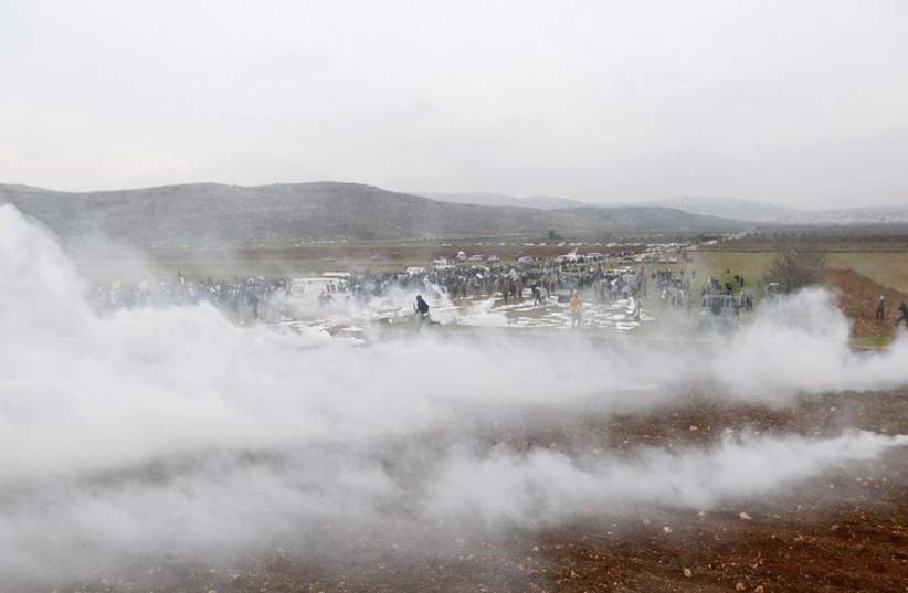 Protesters run away from tear gas fired by Israeli troops during clashes following a demonstration against Israeli settlements near Ramallah (photo credit: REUTERS)