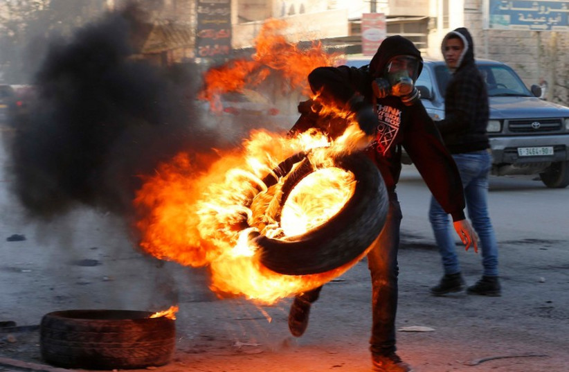 A Palestinian carries a burning tire during clashes with Israeli troops following the funeral of Palestinian Mahmoud Adwan at Qalandia checkpoint near the West Bank city of Ramallah (photo credit: REUTERS)