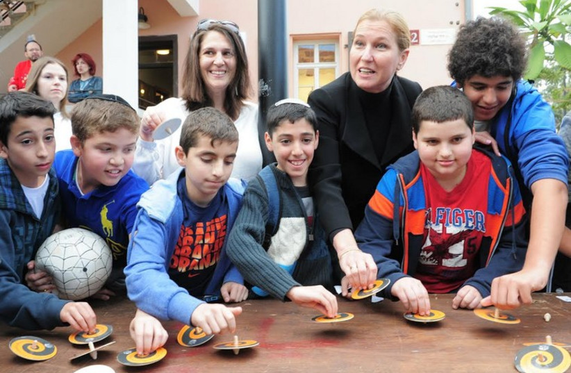 MK Tzipi Livni and a group of children at the Guinness world record dreidel challenge in Tel Aviv (photo credit: KFIR SIVAN)