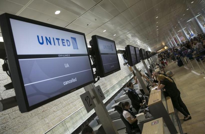 Passengers stand near a check-in desk at Ben-Gurion International Airport, near Tel Aviv (photo credit: REUTERS)