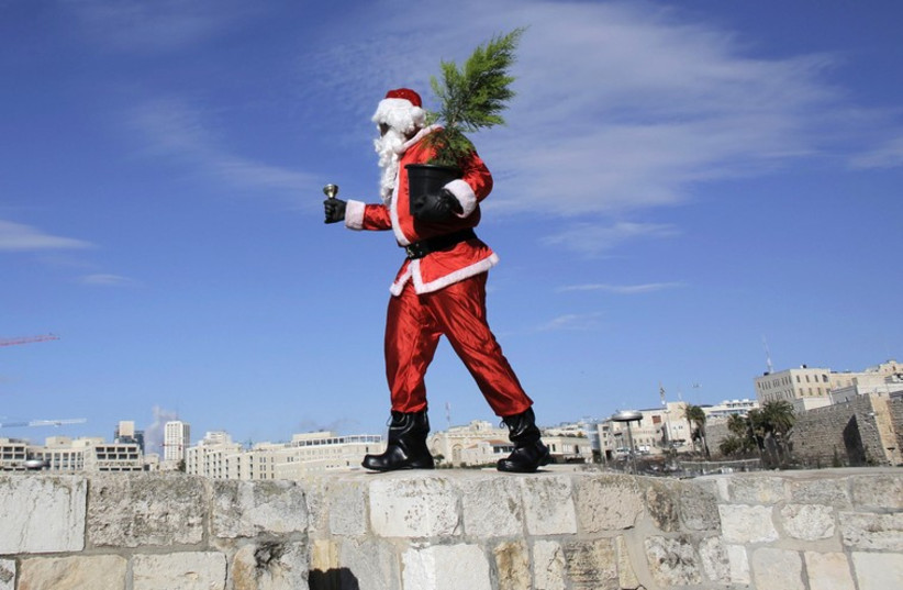 Santa distributes free Christmas trees in the Old City. (photo credit: REUTERS)