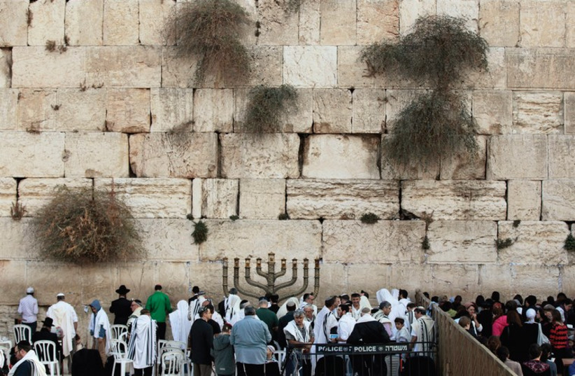 WORSHIPERS PRAY at the Western Wall in the capital during Hanukka last year. (photo credit: REUTERS)