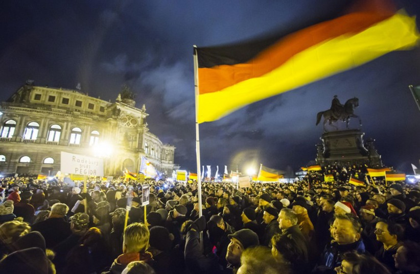 Participants hold German national flags during a demonstration organized by anti-immigration group Pediga at Dresden. (photo credit: REUTERS)