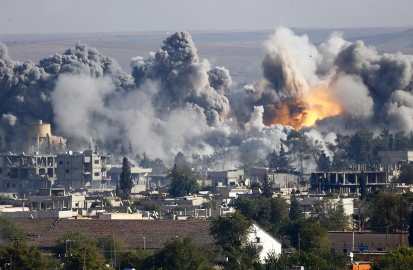 Smoke rises over Syrian town of Kobani after an airstrike (photo credit: REUTERS)