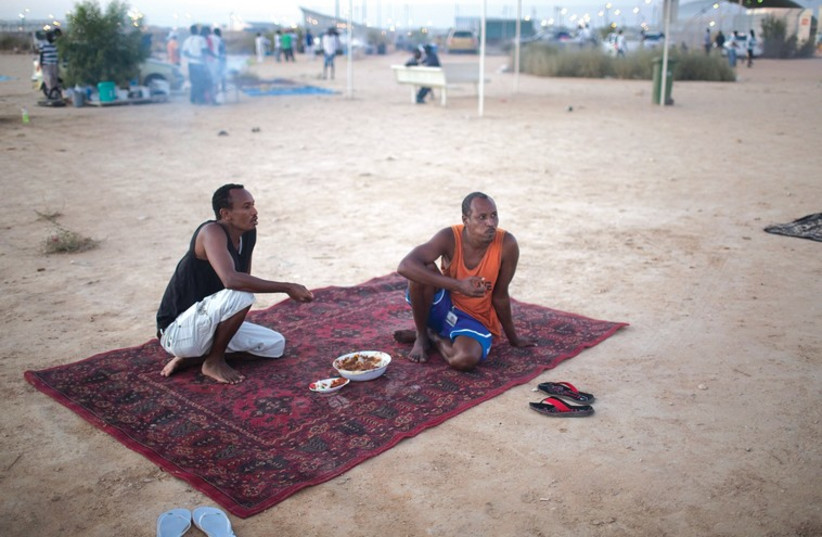 Migrants eat dinner outside the Holot open detention facility. (photo credit: REUTERS)