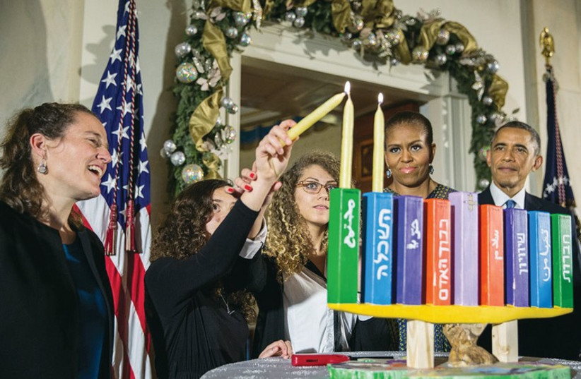Barack Obama and first lady Michelle Obama as they light a Hanukka made by pupils from Jerusalem's Hand in Hand school, at the White House. (photo credit: REUTERS)