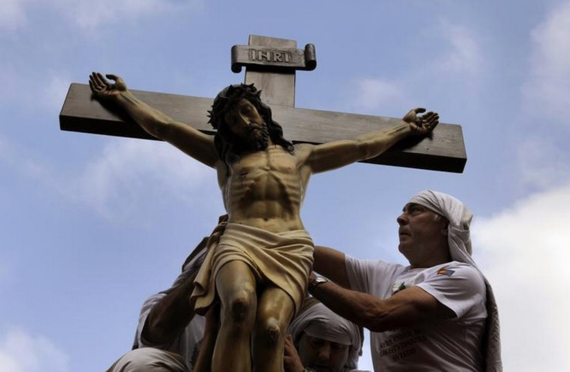 """Penitents place a statue of Jesus Christ on top of a float during the Palm Sunday procession of the """"Estudiantes"""" brotherhood in Oviedo, northern Spain (photo credit: REUTERS)"""
