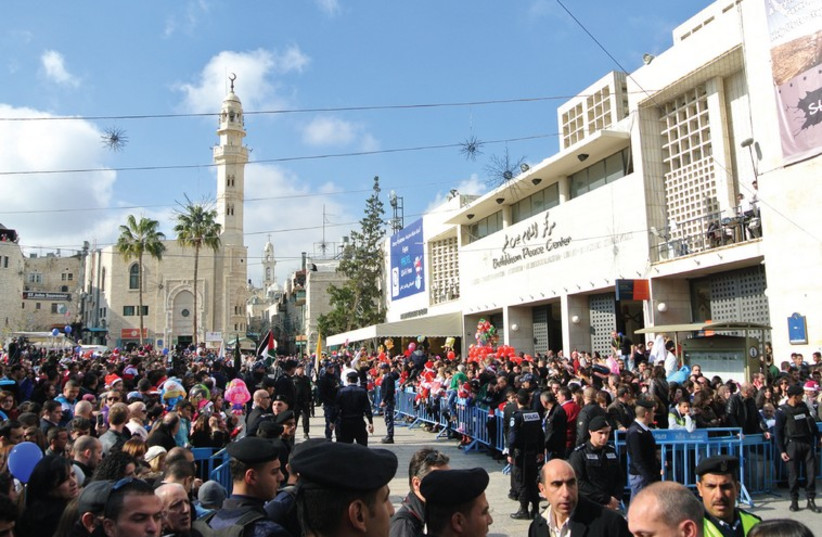 THOUSANDS OF Palestinians and foreign visitors await the arrival of the Latin Patriarch at Manger Square in Bethlehem on Christmas eve. (photo credit: SETH J. FRANTZMAN)