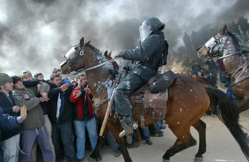 Mounted Israeli police scuffle with pro-settler supporters at the Amona outpost, February 1, 2006 (photo credit: REUTERS)