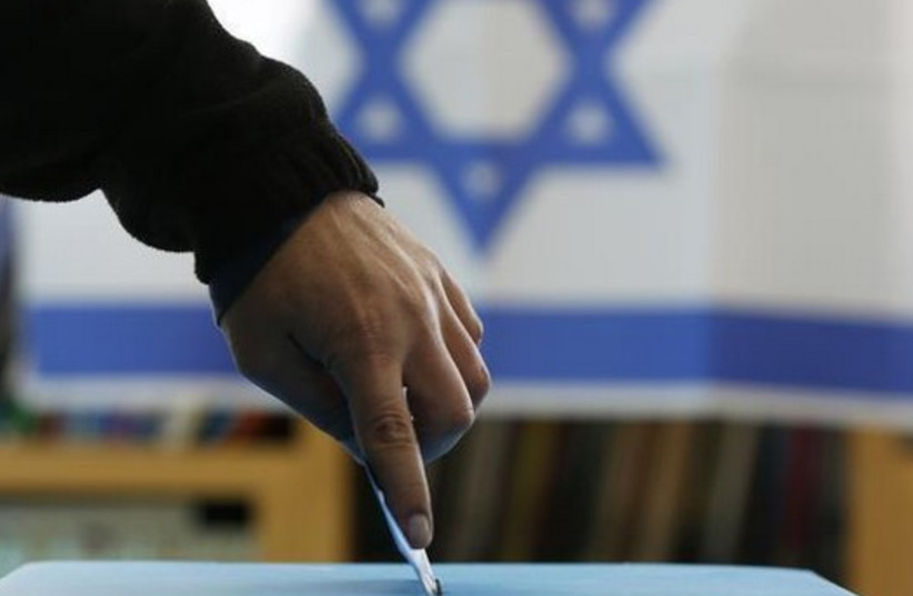 An Israeli flag is seen in the background as a man casts his ballot for the parliamentary election (photo credit: REUTERS)