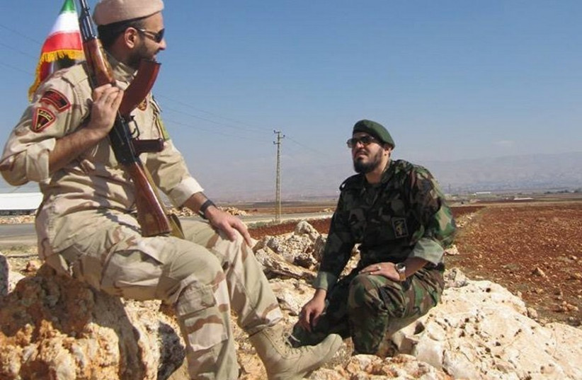 An Iranian Revolutionary Guards soldier and a Hezbollah gunman pose near the Lebanese border with Israel (photo credit: TWITTER)