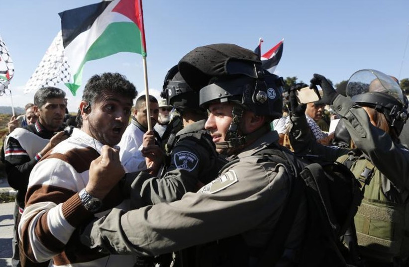 A Palestinian protester confronts a Border Police officer during an anti-settlement protest in the West Bank (photo credit: REUTERS)