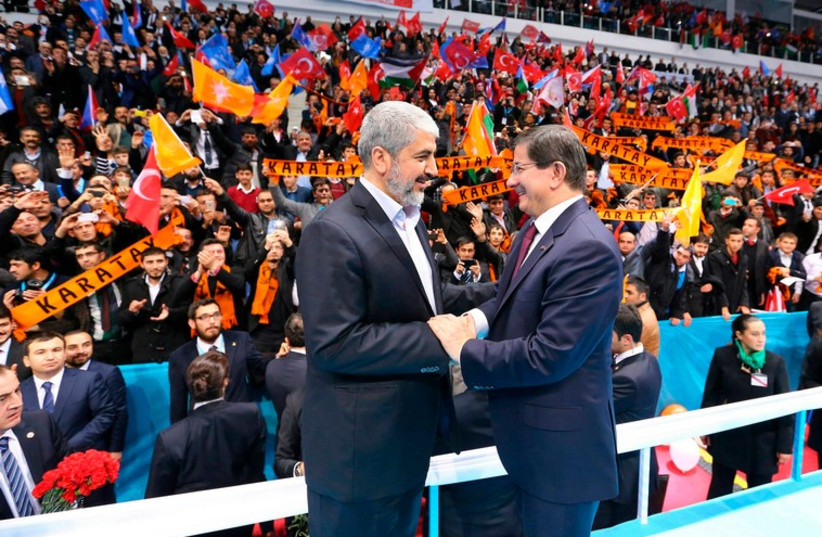 Senior Hamas leader Khaled Mashal shakes hands with Turkish Prime Minister Ahmet Davutoglu during a meeting of Turkey's ruling AK Party (AKP) December 27 (photo credit: REUTERS)