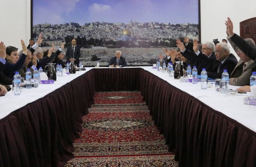Palestinian Authority President Mahmoud Abbas (C) meets with the Palestinian leadership to sign agreements in Ramallah (photo credit: REUTERS)