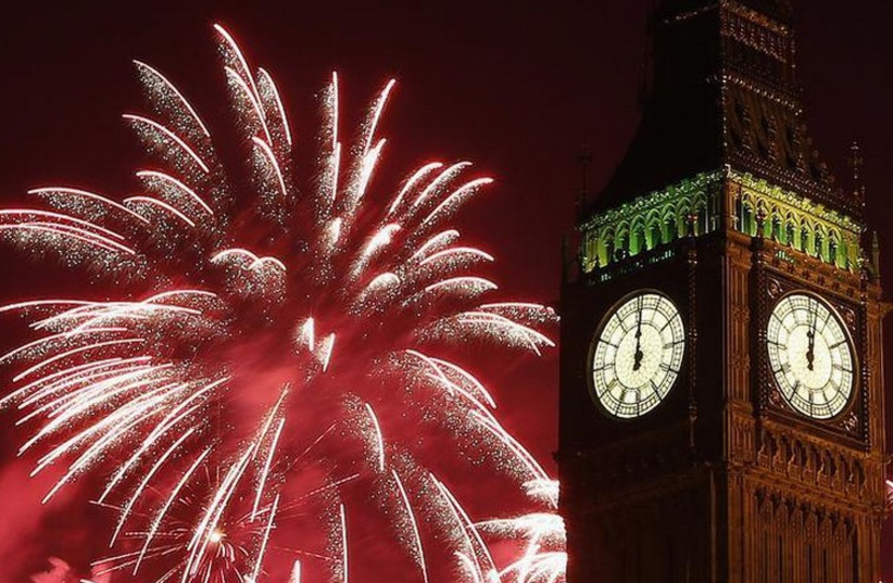 Fireworks explode behind the Houses of Parliament and Big Ben on the River Thames during New Year's celebrations in London (photo credit: REUTERS)