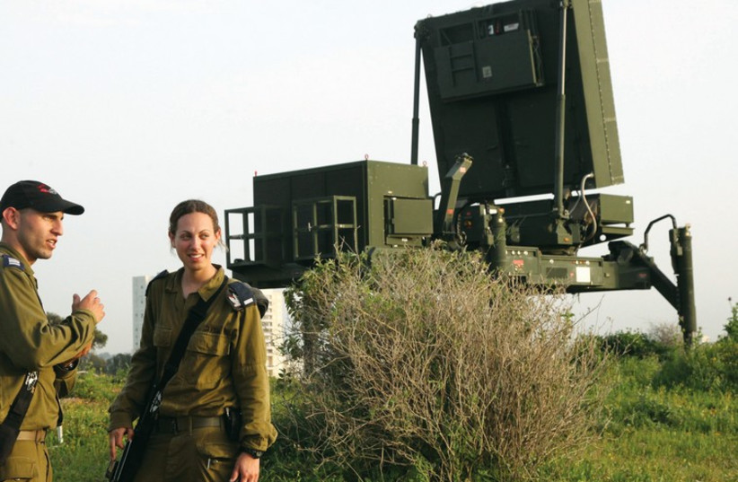 Soldiers stand near the Iron Dome missile defense system outside Tel Aviv. (photo credit: MARC ISRAEL SELLEM/THE JERUSALEM POST)