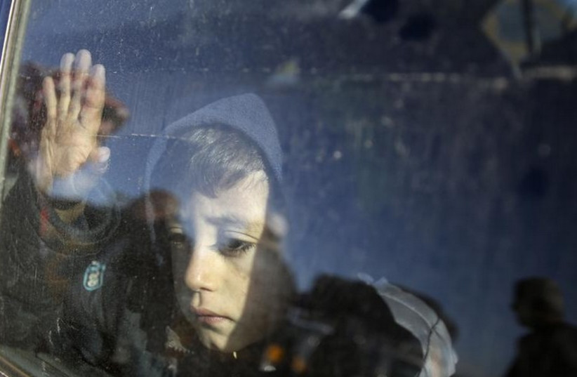 A Palestinian boy, hoping to cross into Egypt with his family, looks out a car window as he waits at the Rafah crossing between Egypt and the southern Gaza Strip (photo credit: REUTERS)