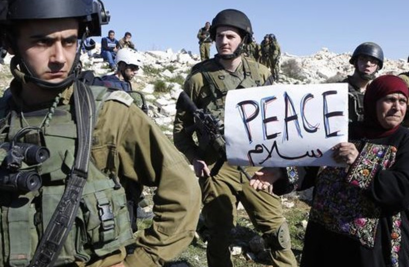 A protester holds a placard as she stands next to Israeli soldiers during a protest against Israeli settlements in Beit Fajjar town south of the West Bank city of Bethlehem (photo credit: REUTERS)