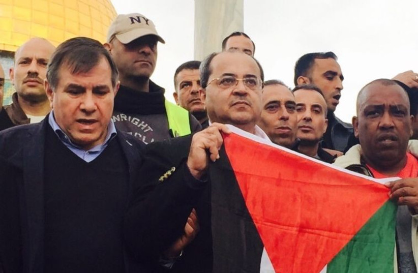 UAL-Ta'al MK Ahmad Tibi holds a Palestinian flag on Temple Mount (photo credit: Courtesy)