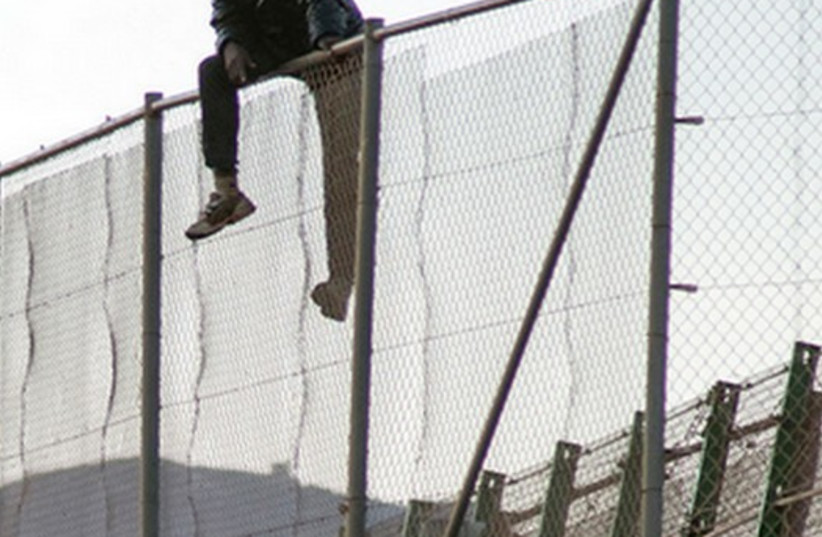 A MAN sits on a fence in Melilla, a Spanish enclave in North Africa. Those successfully scaling the fence are entitled to apply for asylum. (photo credit: REUTERS)