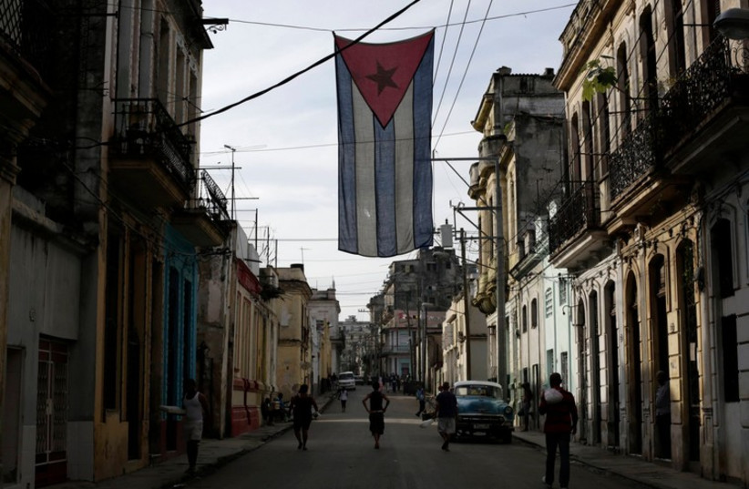 A Cuban flag hangs from a building in Havana (photo credit: REUTERS)