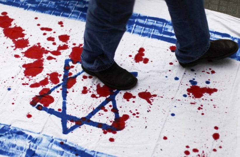 A Venezuelan student walks over a cloth with red paint and the Star of David during an anti-Israel demonstration in Caracas. (photo credit: REUTERS)