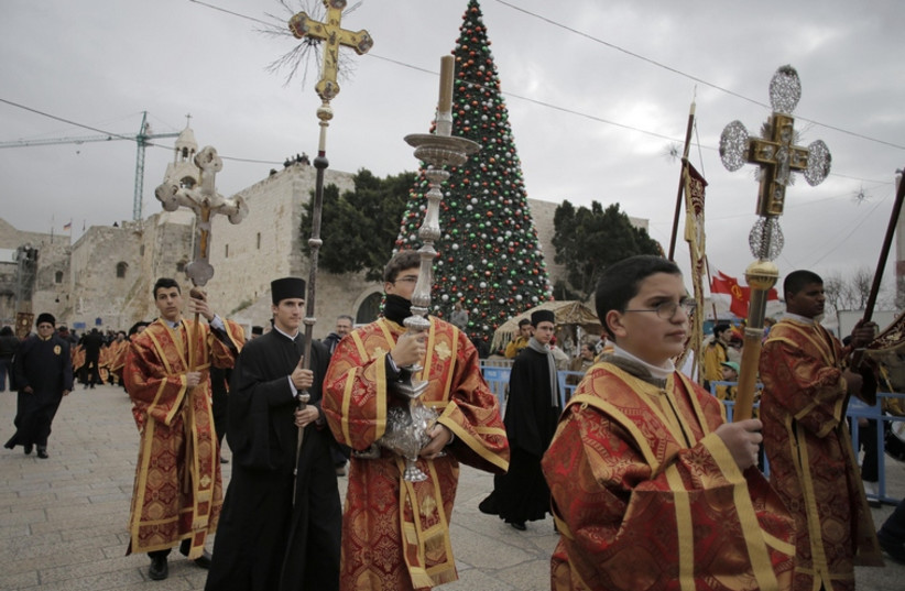 Members of the Greek Orthodox clergy wait for the arrival of the Greek Patriarch of Jerusalem Metropolitan Theophilos before the Eastern Orthodox Christmas procession outside the Church of the Nativity in the West Bank town of Bethlehem (photo credit: REUTERS)