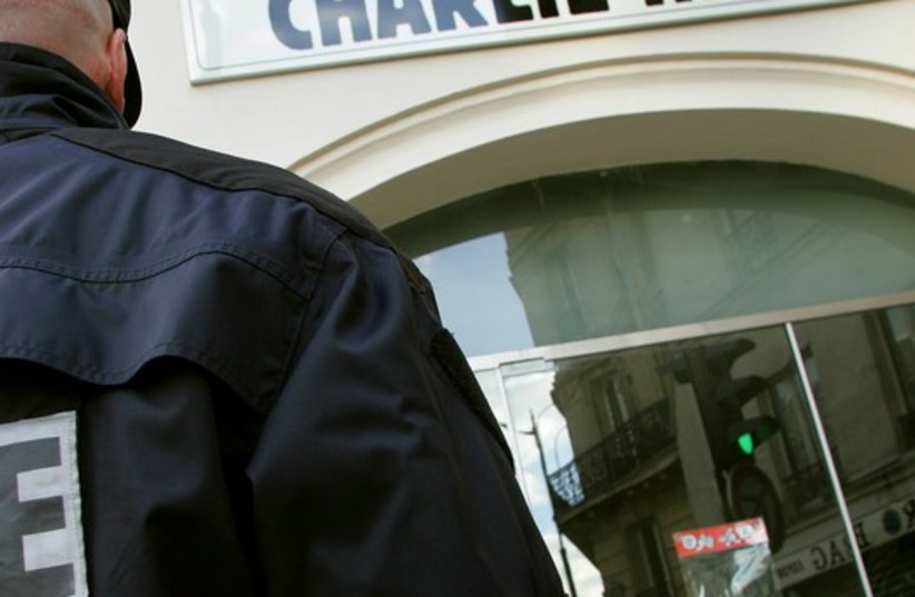 """A policeman stands guard outside the French satirical weekly """"Charlie Hebdo"""" in Paris, February 9, 2006. (photo credit: REUTERS)"""