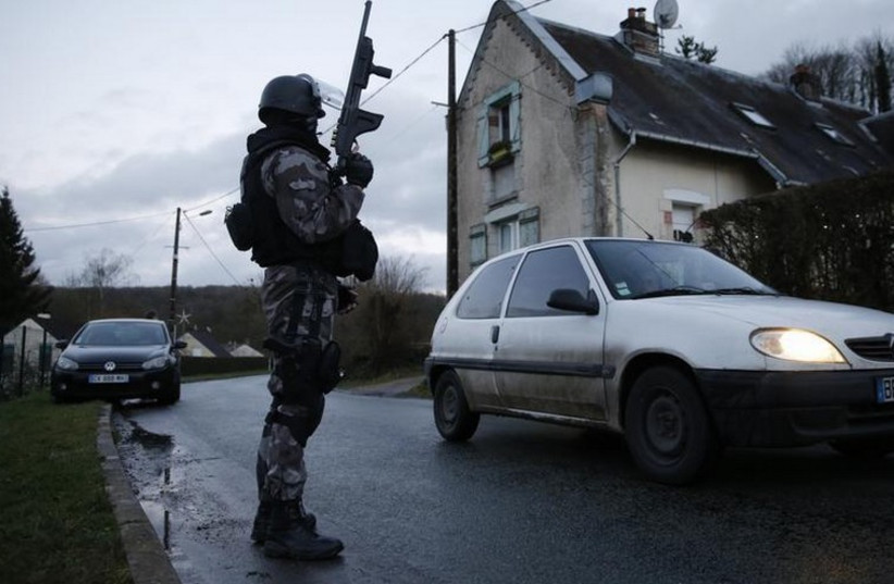 A member of the French GIPN intervention police forces secures a neighborhood in Corcy, northeast of Paris (photo credit: REUTERS)