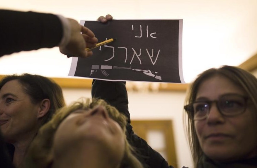 """A woman holds a placard that reads """"I Am Charlie"""" in Hebrew during a memorial service at the residence of France's ambassador to Israel in Jaffa (photo credit: REUTERS)"""