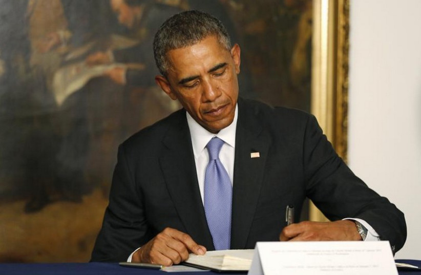 US President Barack Obama signs a condolences book as he pays his respects for victims of the attack at the French newspaper Charlie Hebdo (photo credit: REUTERS)