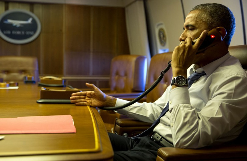 President Barack Obama talks on the phone with French President Francois Hollande from aboard Air Force One, Jan. 7, 2015. (photo credit: OFFICIAL WHITE HOUSE PHOTO / PETE SOUZA)