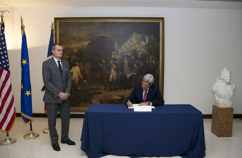 US Secretary of State John Kerry signs a book of condolences for the attack in Paris, at the French Embassy in Washington, D.C., January 9, 2015.  (photo credit: STATE DEPARTMENT PHOTO)