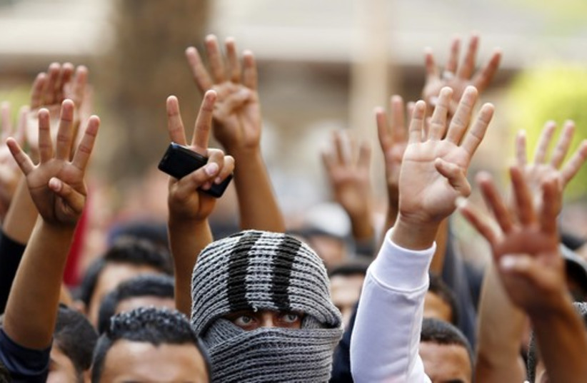 The Rabaa sign is flashed, symbolizing support for the Muslim Brotherhood (photo credit: REUTERS)