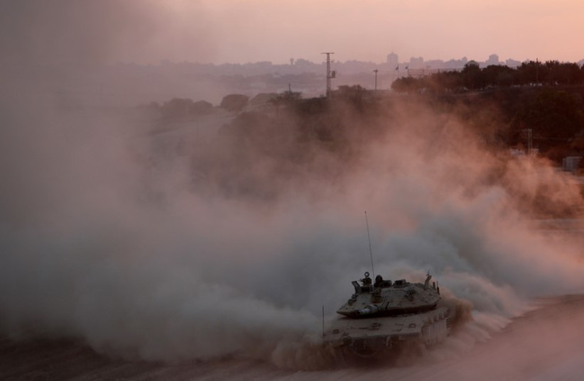 An Israeli tank drives as it returns to Israel from the Gaza Strip August 3, 2014 (photo credit: REUTERS)
