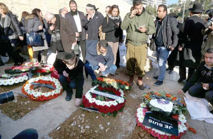 MOURNERS PAY THEIR RESPECTS at the capital's Har Hamenuhot cemetery yesterday at the graves of the victims of the Paris Hyper Cacher terrorist attack. (photo credit: MARC ISRAEL SELLEM/THE JERUSALEM POST)