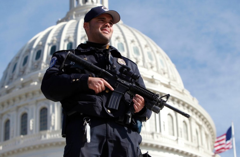 A US Capitol police officer keeps watch in front of the Capitol in Washington [File] (photo credit: REUTERS)