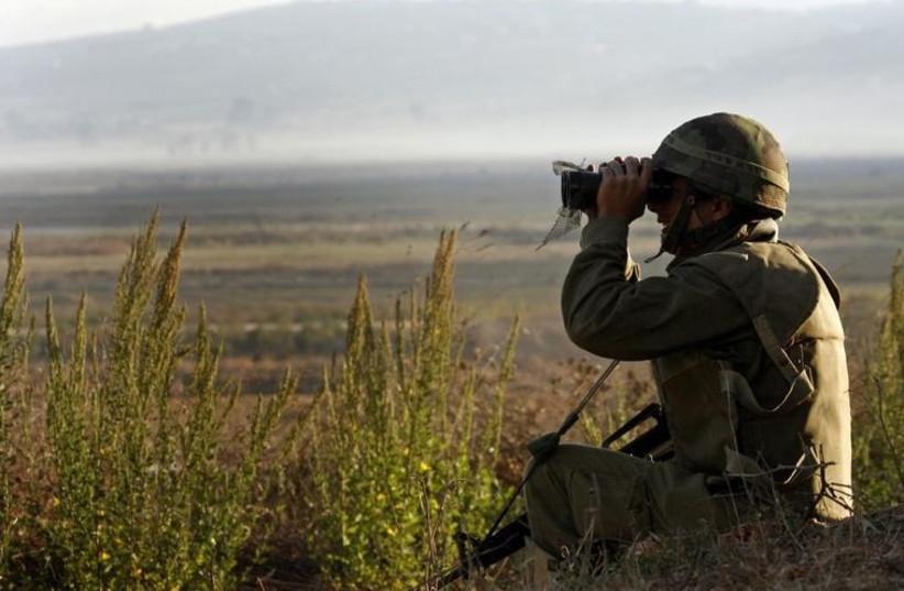 An IDF soldier looks through binoculars (photo credit: REUTERS)