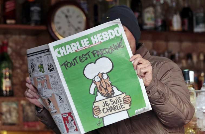 A man poses with the new issue of French satirical weekly Charlie Hebdo at a cafe in Nice. (photo credit: REUTERS)