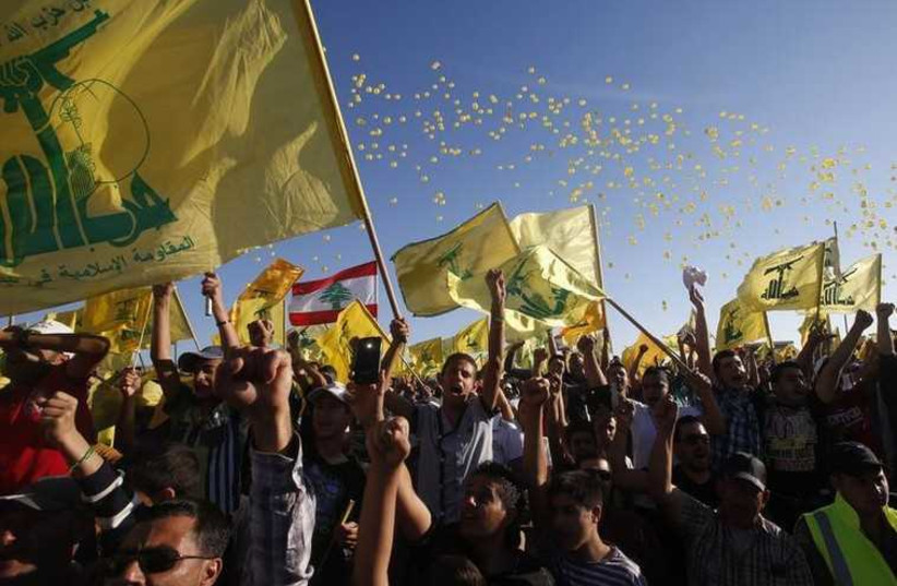People cheer while carrying Hezbollah flags as they celebrate Resistance and Liberation Day in Bint Jbeil (photo credit: REUTERS)