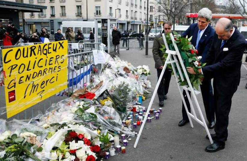 US Secretary of State John Kerry lays a wreath with French Foreign Minister Laurent Fabius at the site of an attack at a Jewish supermarket in Paris January 16 (photo credit: REUTERS)
