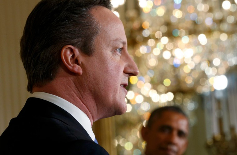 British Prime Minister David Cameron speaks as US President Barack Obama looks on at the White House (photo credit: REUTERS)