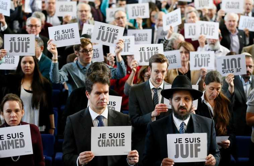 """Members of the Board of Deputies of British Jews hold up signs reading """"I am Charlie,"""" """"I am Jewish"""" and """"I am Ahmed,"""" during an event in London (photo credit: REUTERS)"""