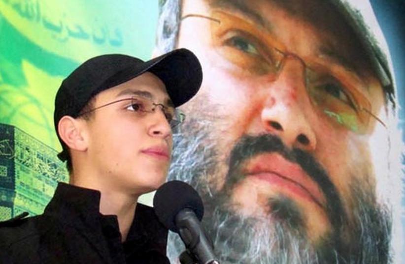 Jihad Mughniyeh stands in front of photo of his slain father, Hezbollah commander Imad Mughniyeh (photo credit: ARAB MEDIA)