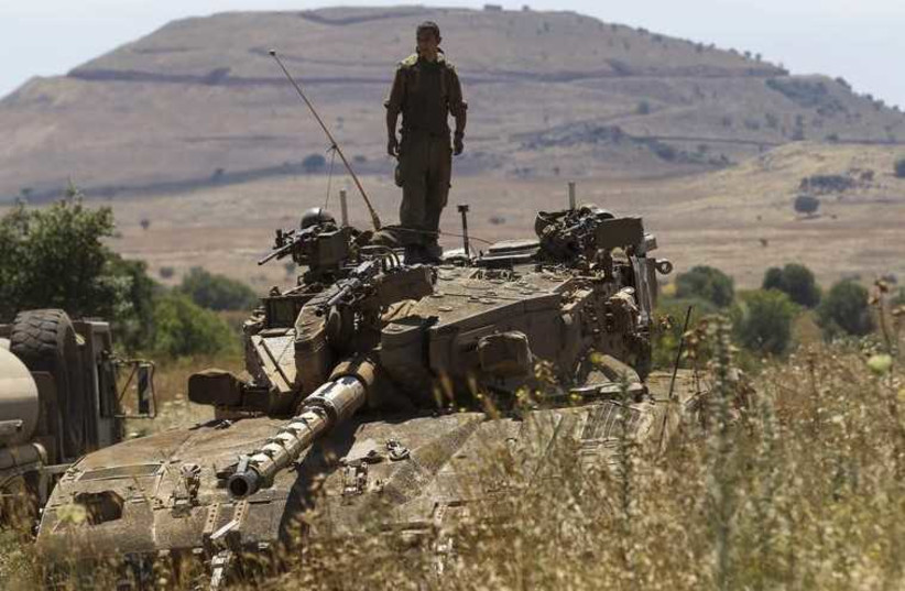 An IDF soldier stands atop a tank near Alonei Habashan on the Golan Heights, close to the ceasefire line between Israel and Syria (photo credit: REUTERS)