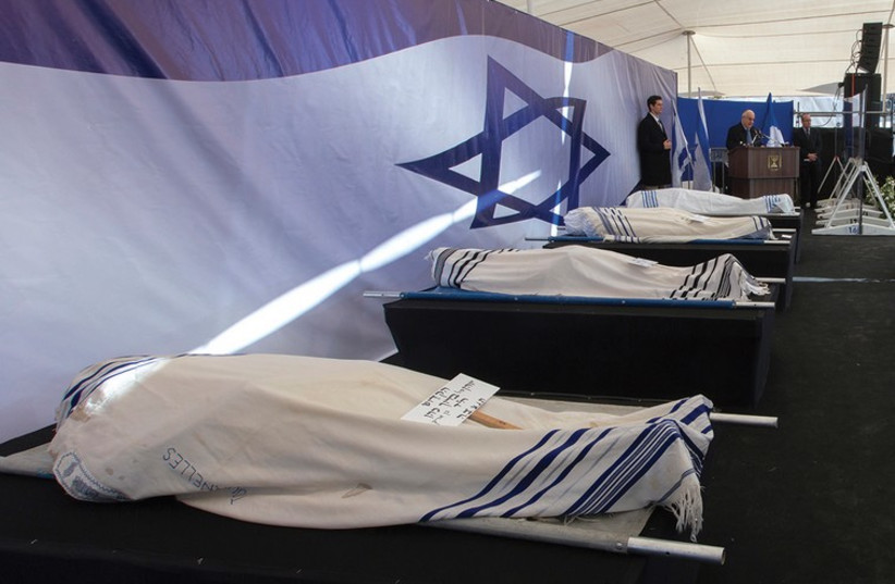 PRESIDENT REUVEN Rivlin delivers a speech near the covered bodies of Yohan Cohen, Yoav Hattab, Philippe Braham and Francois-Michel Saada, victims of Friday's attack on a Paris grocery, during their joint funeral in Jerusalem. (photo credit: REUTERS)